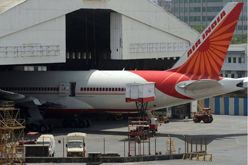 """A jeep goes past an Air India aircraft parked at Chattrapati Shivaji International airport in Mumbai on May 8, 2012. At least 100 pilots from India's debt-laden national carrier Air India failed to turn up to work in a move the civil aviation minister described as an """"illegal"""" strike.  The airline, which loses nearly USD 2 million a day, is facing mounting problems due to rising fuel prices, competition from low-cost rivals and a record of labour disputes. AFP PHOTO/Indranil MUKHERJEE"""