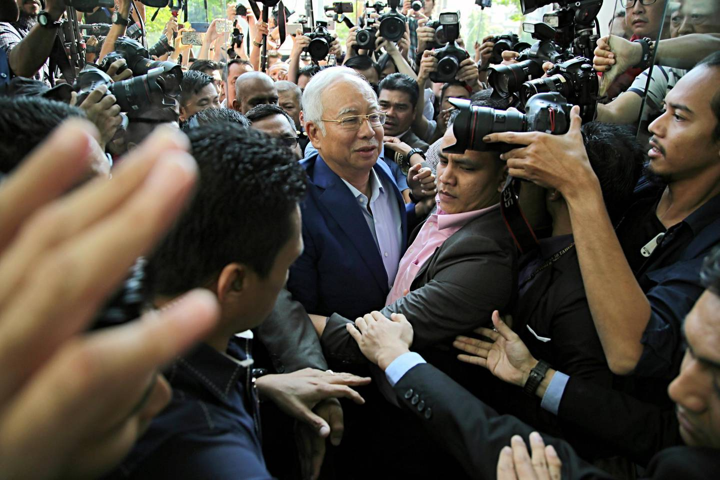 Najib Razak, Malaysia's former prime minister, center, is surrounded by members of the media as he arrives at the Malaysian Anti-Corruption Commission's headquarters in Putrajaya, Malaysia, on Tuesday, May 22, 2018. Najibis at the center of investigations looking into theMalaysian state investment fund known as 1MDB and whether it was used for embezzlement or money laundering. Photographer: Rahman Roslan/Bloomberg