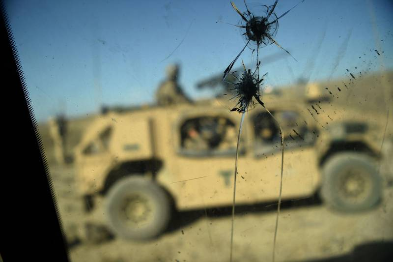 """(FILES) In this file photo taken on July 7, 2018, US Army soldiers from NATO are seen through a cracked window of an armed vehicle in a checkpoint during a patrol against Islamic State militants at the Deh Bala district in the eastern province of Nangarhar Province.  The US military claims to have """"successfully"""" disrupted the online propaganda efforts of the Islamic State in a hacking operation dating back at least to 2016, according to declassified national security documents released on January 21, 2020. The heavily redacted, previously top secret documents said the US Cyber Command """"successfully contested ISIS in the information domain"""" and limited its online efforts on radicalization and recruitment """"by imposing time and resource costs"""" on the jihadist group.  / AFP / WAKIL KOHSAR"""