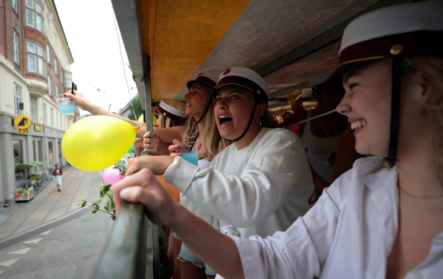 """Danish students celebrate """"Studenterkorsel"""" an event to mark the finishing of high school, as they travel on an open-backed truck through the city, stopping along the route to visit their parents' houses to drink and eat snacks, in Copenhagen, Denmark, June 25, 2021. Picture taken June 25, 2021. REUTERS/Hannah McKay"""