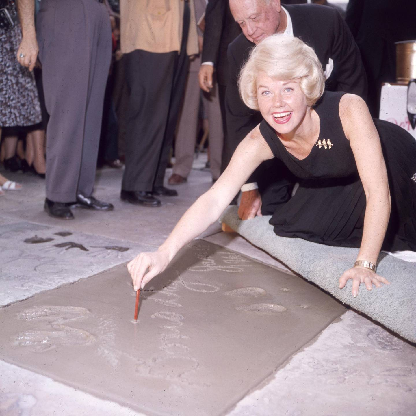 19th January 1961:  American singer and actress Doris Day smiling as she signs her name in cement by her handprints, in front of Mann's (formerly Grauman's) Chinese Theater, on Hollywood Boulevard, Hollywood, California.  (Photo by Hulton Archive/Getty Images)