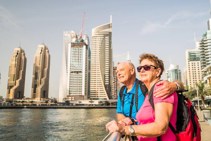 happy smiling active senior tourist couple together on sightseeing vacation through United Arab Emirates