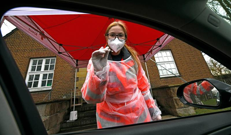 A Red Cross worker in protective clothes prepares to administer a COVID-19 rapid test at a coronavirus test drive-in in Gelsenkirchen, Germany, Wednesday, March 17, 2021. The German federal government offers one free rapid test per week for every citizen. (AP Photo/Martin Meissner)