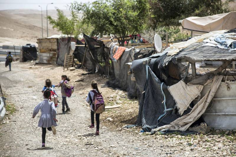 Beduin children pass by the shanty homes  in the tiny West Bank Beduin village of Khan al-Ahmar  on May 2,2018.The Israeli Supreme Court is expected next week to rule on the fate of the village, situated east of Jerusalem between the expanding settlements of Maale Adumim and Kfar Adumim.  The Israeli state says Khan al-Ahmar must be leveled because its structures are situated on state land and were built without permits, which are nearly impossible to obtain in the part of the West Bank known as area C, under full Israeli control.(Photo by Heidi Levine for The National).
