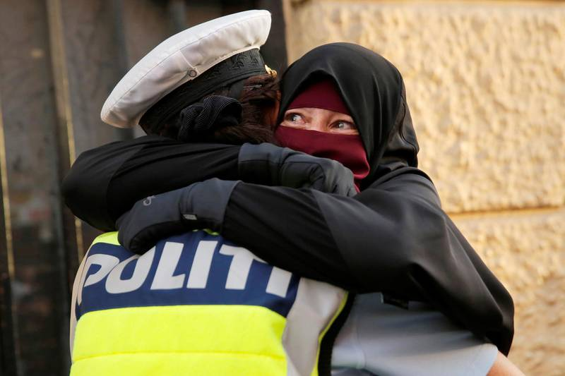 QUALITY REPEAT - Ayah, 37, (R) and wearer of the niqab weeps as she is embraced by a police officer during a demonstration against the Danish face veil ban in Copenhagen, Denmark, August 1, 2018.  REUTERS/Andrew Kelly
