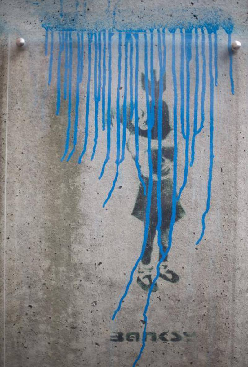 epa04636990 View at the damaged graffiti 'Bomb Hugger' by British streetart artist Banksy in Hamburg, Germany, 25 February 2015. Unkowns destroyed the only graffiti of Banksy in Hamburg. The perpretators had sprayed the word 'Graffiti'and a blue line above the artwork.  EPA/CHRISTIANCHARISIUS