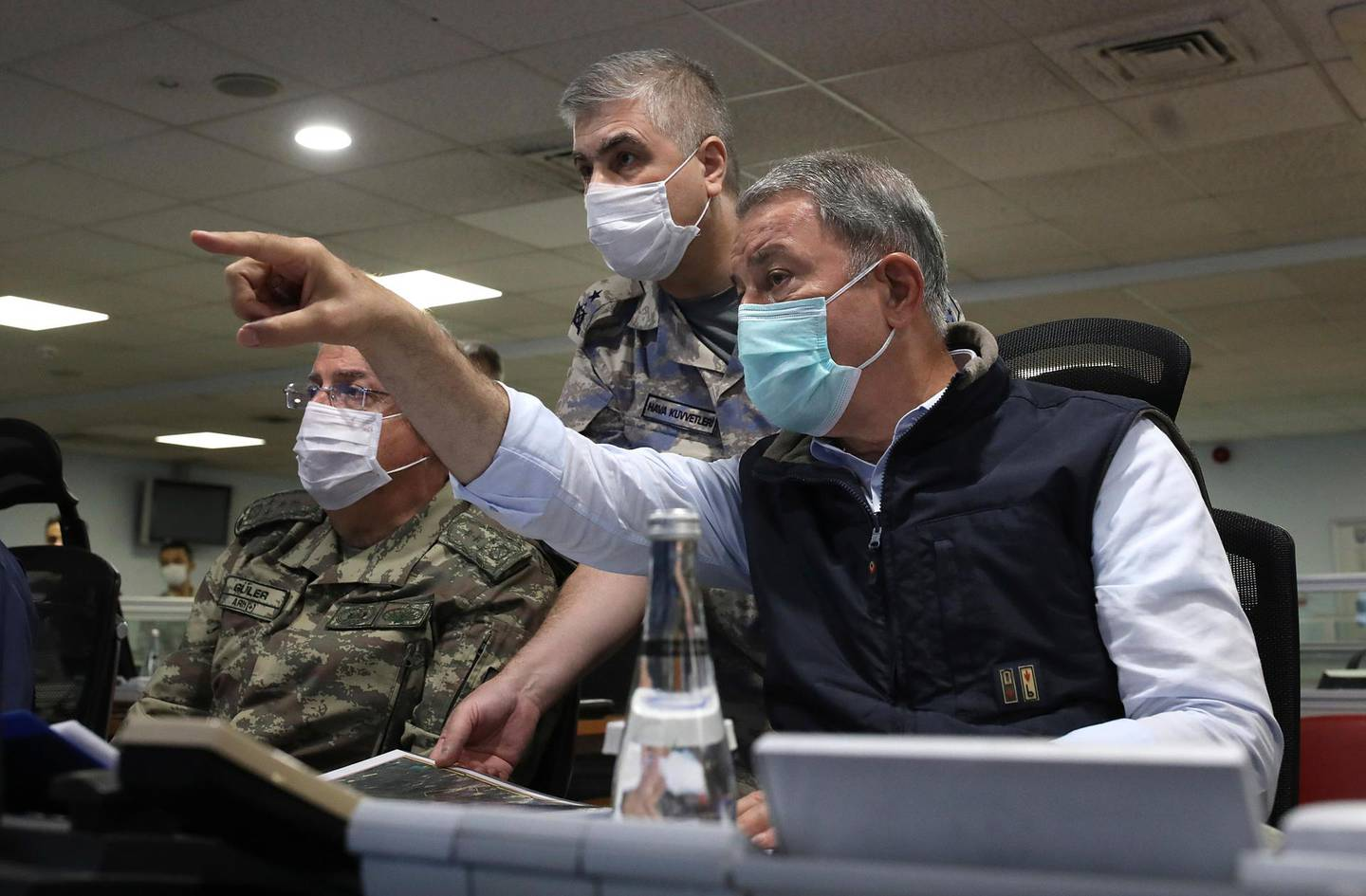 Turkish Defense Minister Hulusi Akar, right, and army commanders wearing face masks to protect against the coronavirus, speak at a military headquarter, in Ankara, Turkey, Monday, June 15, 2020. Turkey's jets have carried out new cross-border air strikes against outlawed Kurdish rebel targets in northern Iraq, the Turkish Defense Ministry said Monday. (Turkish Defense Ministry via AP, Pool)
