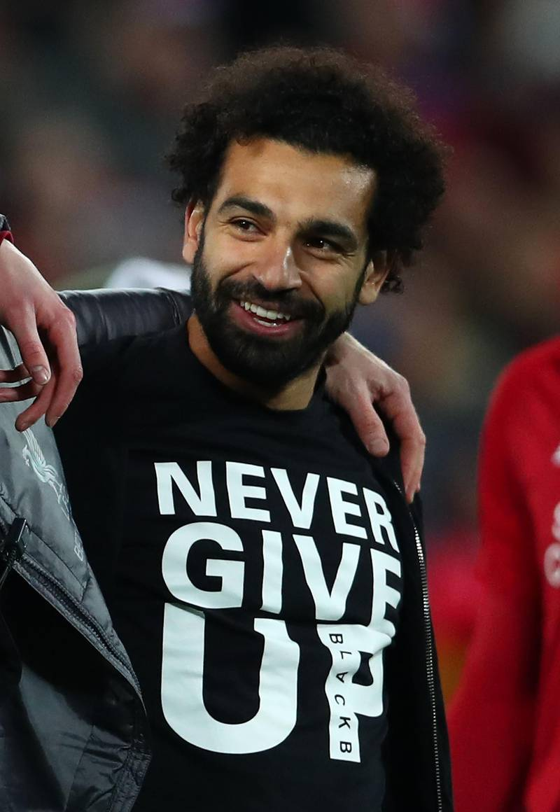 LIVERPOOL, ENGLAND - MAY 07:  Mohamed Salah of Liverpool celebrates wearing a shirt with the words Never Give Up after the UEFA Champions League Semi Final second leg match between Liverpool and Barcelona at Anfield on May 07, 2019 in Liverpool, England. (Photo by Clive Brunskill/Getty Images)