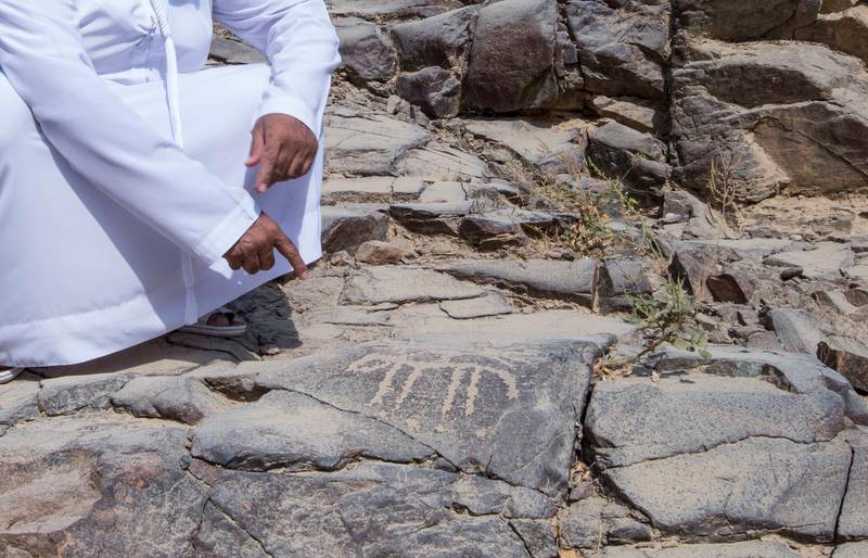 Sharjah, United Arab Emirates-  Abdullah Khilfan Al Naqbi showing what looks to be an ancient drawings carved on a rock at Al Nahwa Village in Sharjah.  Leslie Pableo for The National for Ruba Haza