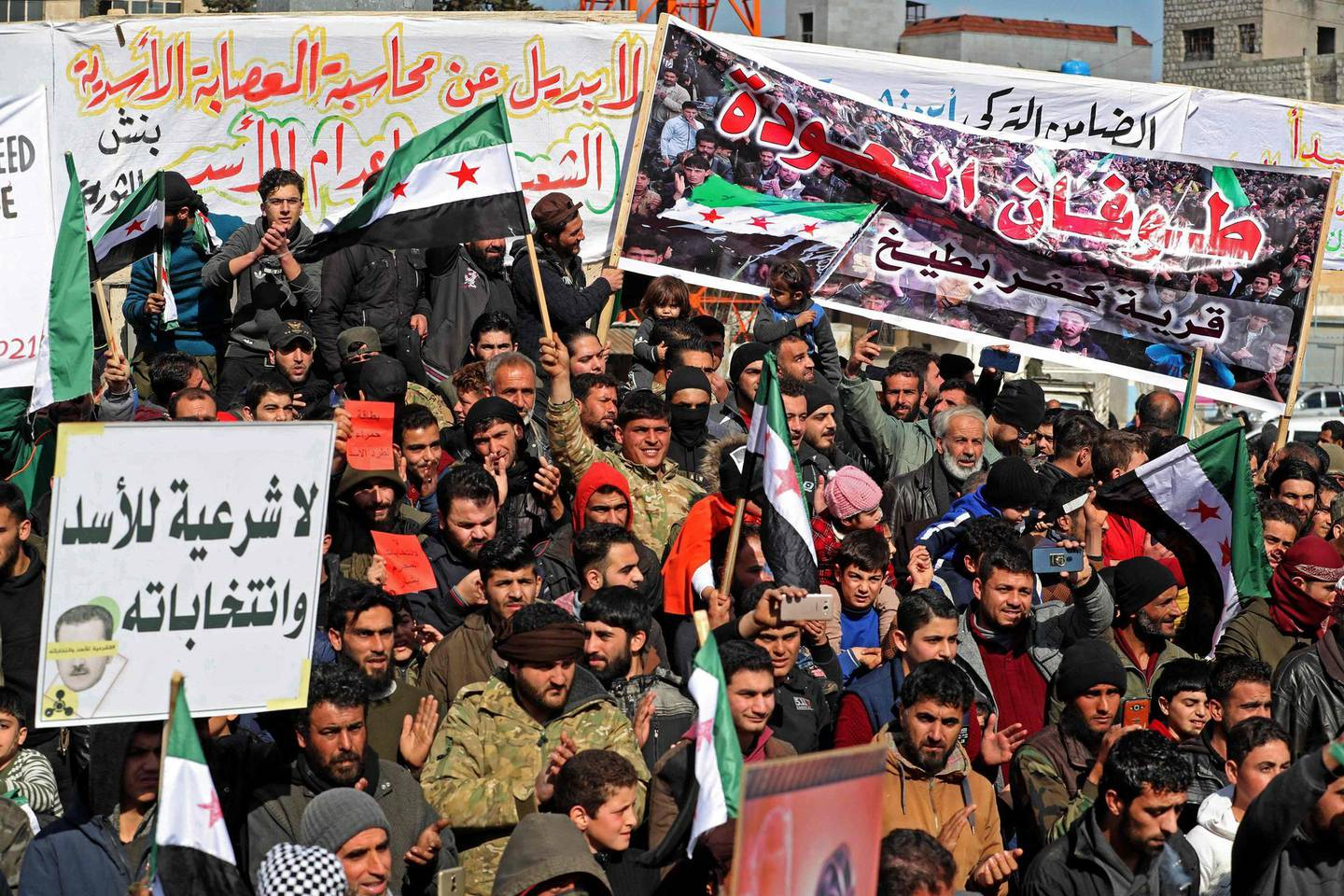 Displaced Syrians demonstrate against President Bashar al-Assad and the upcoming presidential election in the rebel-held city of Idlib on February 19, 2021. / AFP / OMAR HAJ KADOUR