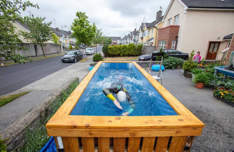 """Irish Paralympic hopeful Leo Hynes, who is legally blind, trains in his home-made training pool in his front garden at home in Tuam, Co Galway, west Ireland, on June 18, 2020. - In his suburban driveway in the west of Ireland, blind triathlete Leo Hynes clambers into a box of water, straps himself to a bungee cord and starts to swim -- going nowhere, but going fast. During coronavirus lockdown, the aspiring paralympian has been unable to train as usual for the now-delayed Tokyo games. Instead he has been finessing his breaststroke in a homemade """"treadmill pool"""" where he is held in place by elastic cords. (Photo by Paul Faith / AFP) / TO GO WITH AFP STORY BY JOE STENSON"""