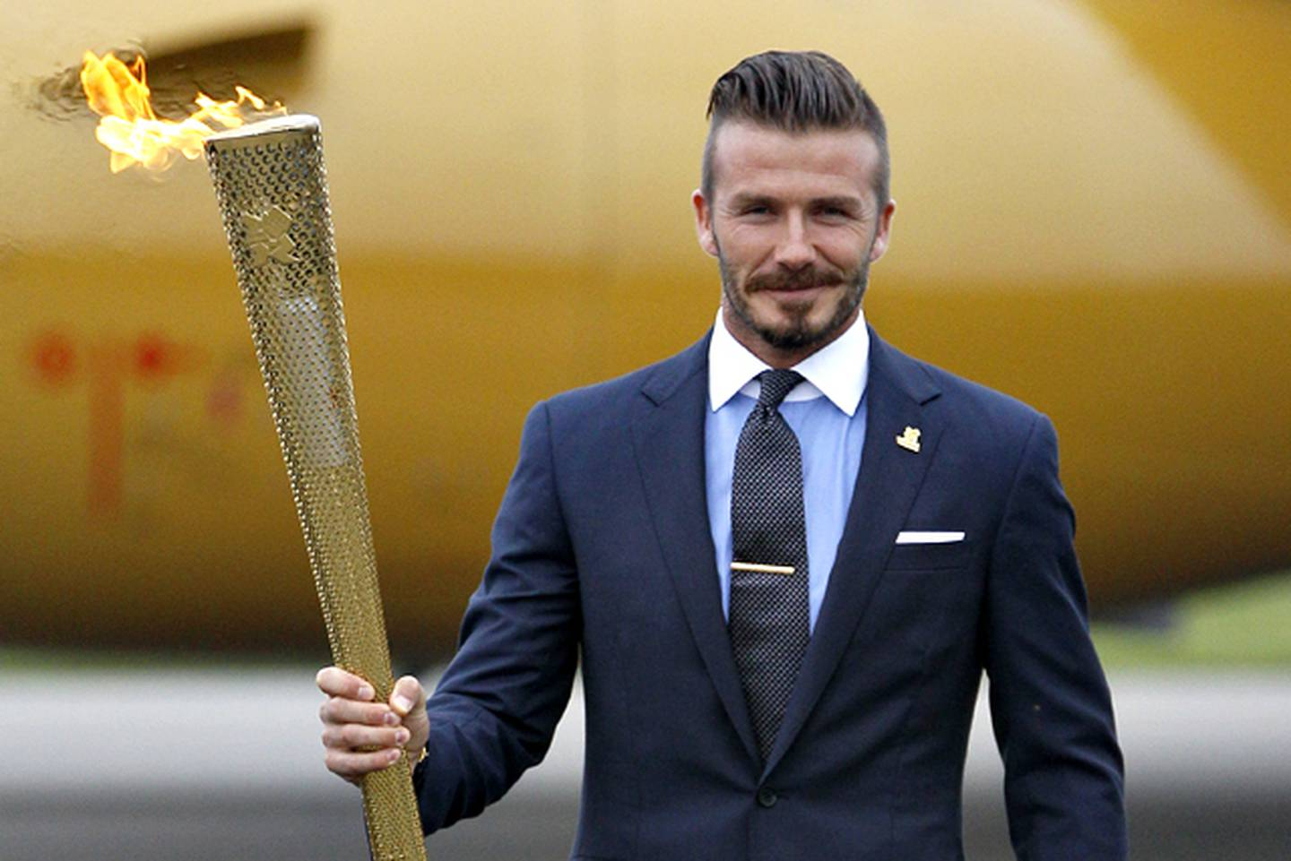Britain's David Beckham holds the Olympic torch during the ceremony to mark the arrival of the Olympic flame to Britain from Greece, at RNAS Culdrose, Cornwall, England, Friday May 18, 2012. (AP Photo/Alastair Grant)