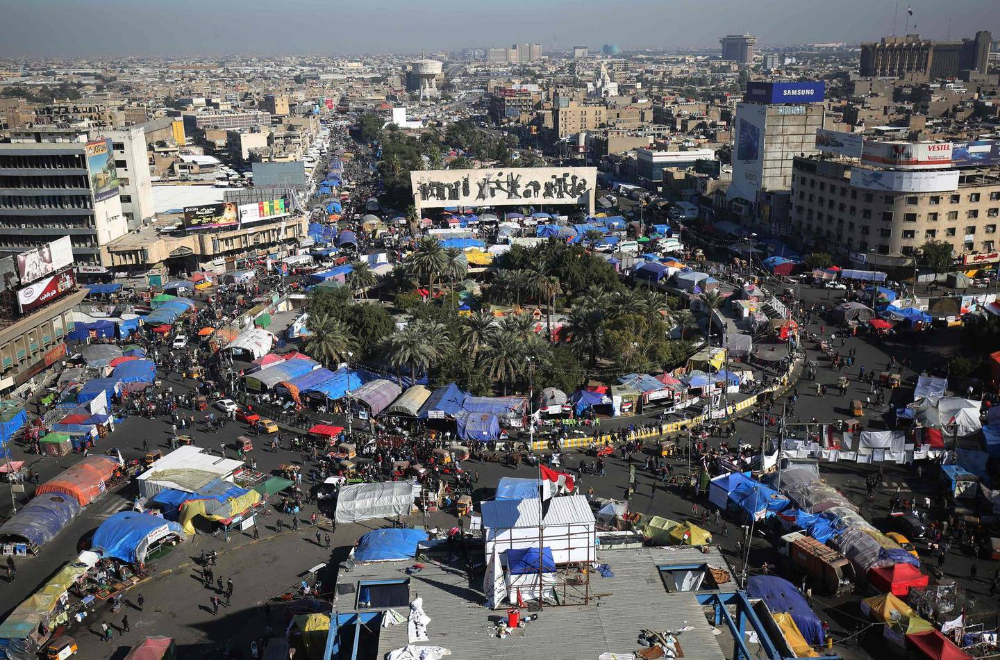 """TOPSHOT - Iraqi demonstrators gather at Tahrir square in the capital Baghdad on December 20, 2019 during ongoing anti-government protests. Iraq's top Shiite cleric Grand Ayatollah Ali Sistani called today for early elections to end the months of political paralysis that have gripped the protest-hit country. """"The quickest and most peaceful way out of the current crisis and to avoid plunging into the unknown, chaos or internal strife ... is to rely on the people by holding early elections,"""" said a representative of Sistani, who never appears in public.  / AFP / AHMAD AL-RUBAYE"""