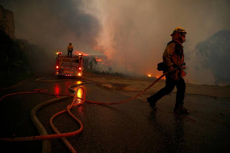 Firefighters battle the Woolsey Fire in Malibu, California, U.S. November 9, 2018. The fire destroyed dozens of structures, forced thousands of evacuations and closed a major freeway. REUTERS/Eric Thayer