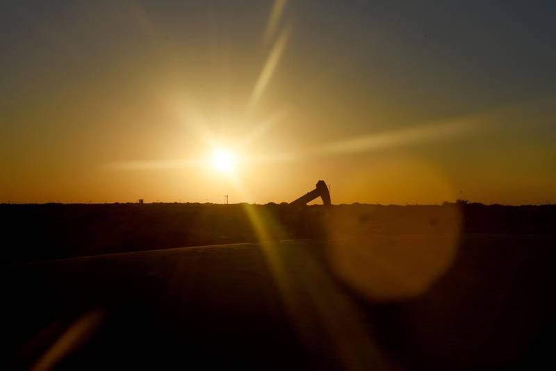 The sun sets behind an oil rig seen from Monahans Sandhills State Park in Monahans, Texas, U.S., on Tuesday, June 19, 2018. In the West Texas plains, frack-sand mines suddenly seem to be popping up everywhere. Twelve months ago, none of them existed - together, these mines will ship some 22 million tons of sand this year to shale drillers in the Permian Basin, the hottest oil patch on Earth. Photographer: Callaghan O'Hare/Bloomberg