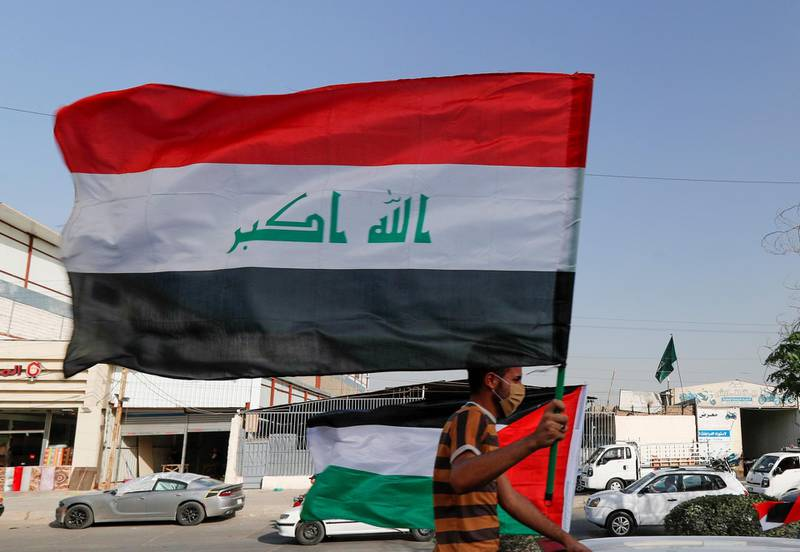 A member of Kataib Hezbollah paramilitary group holds an Iraqi flag and travels in a vehicle as he takes part in a parade ahead of the annual Quds Day, or Jerusalem Day, during the Muslim holy month of Ramadan, in Baghdad, Iraq May 6, 2021. REUTERS/Thaier Al-Sudani