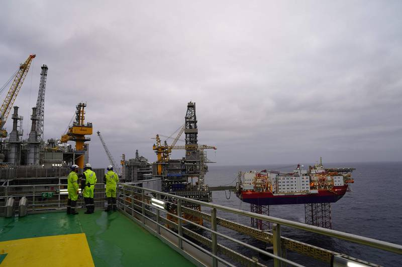 Journalists and employees of Norwegian oil producer Equinor look out at the platforms producing oil above the Johan Sverdrup oilfield during a media visit, in the North Sea 140 kilometres west of the town of Stavanger, Norway, on December 3, 2019. Norway's King Harald will formally inaugurate the field in January 2020, but production began back in early October 2019 and 350,000 barrels are already being pumped up per day.  Fifty years after the Scandinavian country first struck black gold, the field holds the promise of another half-century of oil business, despite growing opposition to fossil fuels.       / AFP / Tom LITTLE / TO GO WITH AFP STORY by Pierre-Henry DESHAYES