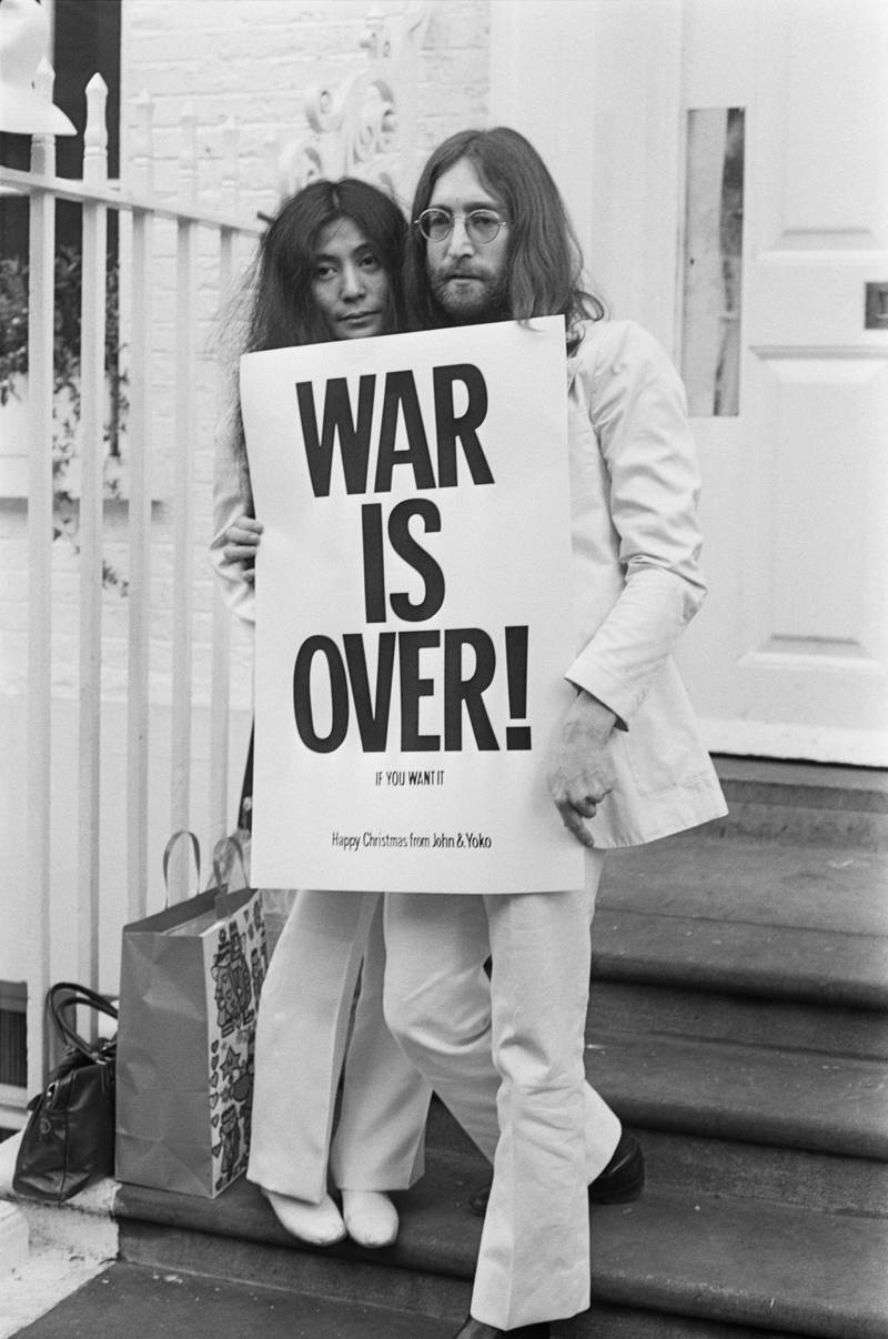 John Lennon (1940 - 1980) and Yoko Ono pose on the steps of the Apple building in London, holding one of the posters that they distributed to the world's major cities as part of a peace campaign protesting against the Vietnam War, December 1969. The poster reads 'War Is Over, If You Want It'. (Photo by Frank Barrett/Keystone/Hulton Archive/Getty Images)