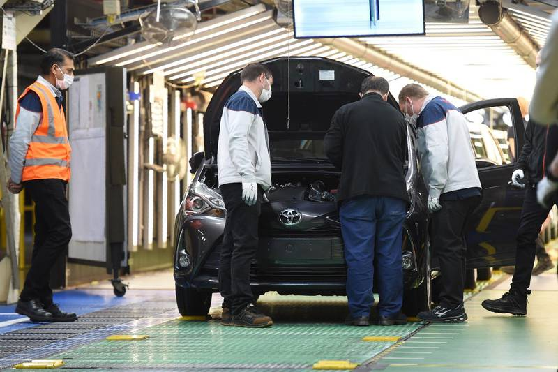 Employees of Toyota, wear protective facemasks and gloves as they work on vehicles at the assembly line of the Toyota automobile plant in Onnaing, near Valenciennes, on April 23, 2020, as the factory reopened after more than a month break aimed at curbing the spread of the COVID-19 (novel coronavirus).  / AFP / FRANCOIS LO PRESTI