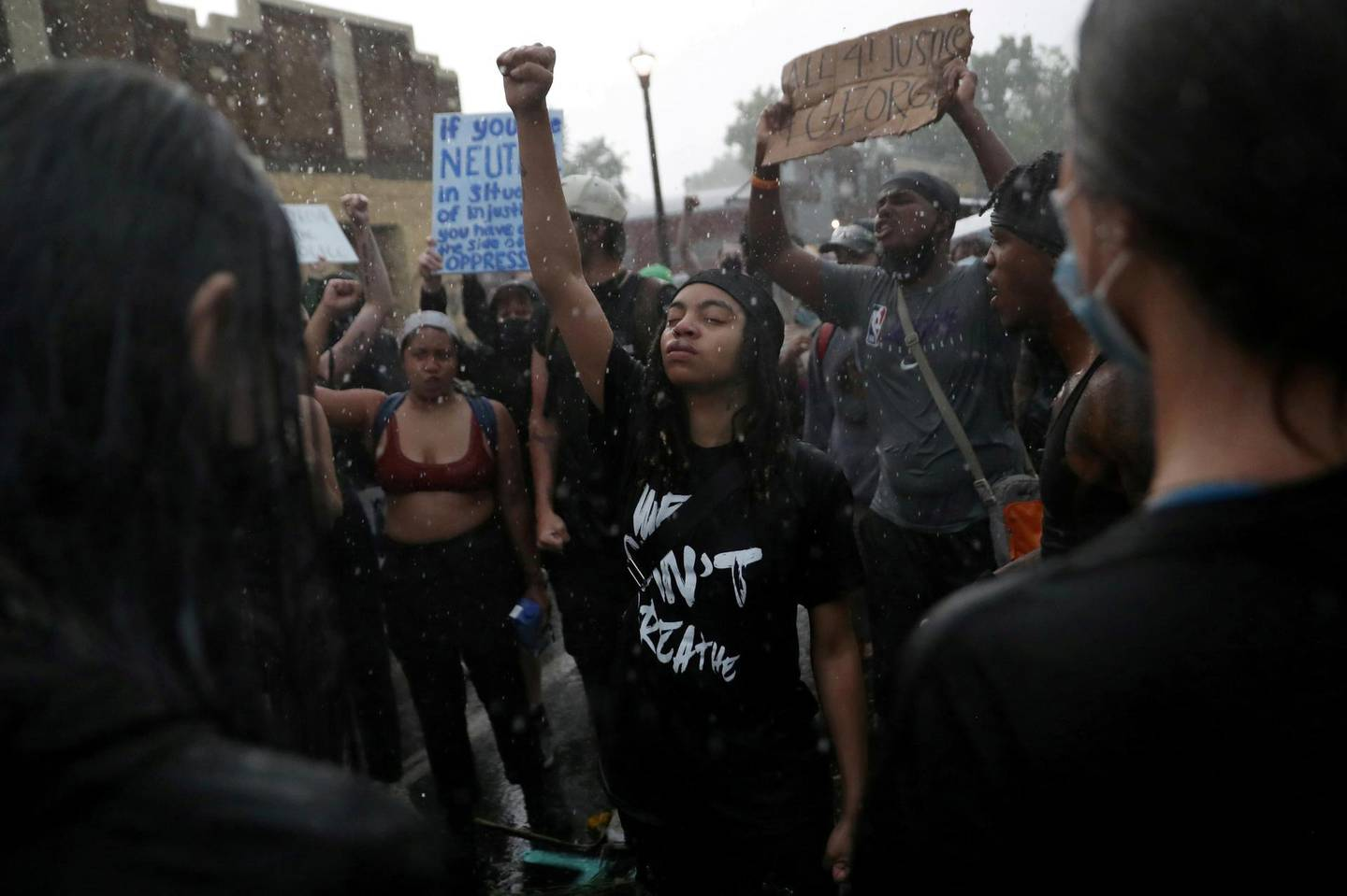 """Rain falls as C'Monie Scott raises her fist while people chant around her at a memorial site for George Floyd that has been created at the place where he was taken into police custody and later pronounced dead, in Minneapolis, Minnesota, U.S., June 2, 2020. REUTERS/Leah Millis/File Photo     SEARCH """"POY BLM"""" FOR THIS STORY. SEARCH """"WIDER IMAGE"""" FOR ALL STORIES. TPX IMAGES OF THE DAY REFILE - CORRECTING NAME"""