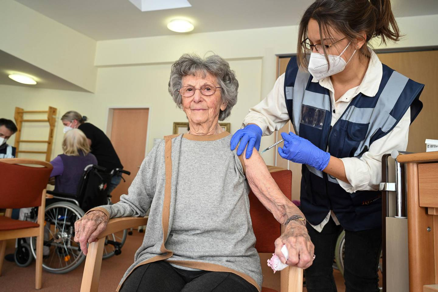 Medical student Mara Karcher vaccinates a resident Ella Holdenried of  Sankt Verena nursing home in Strassberg, Germany, Wednesday, Dec. 30, 2020. German authorities have reported more than 1,000 coronavirus-related deaths in one day for the first time since the pandemic began. The national disease control center, the Robert Koch Institute, said Wednesday that 1,129 more deaths were reported over the past 24 hours. (Felix Kaestle/dpa via AP)