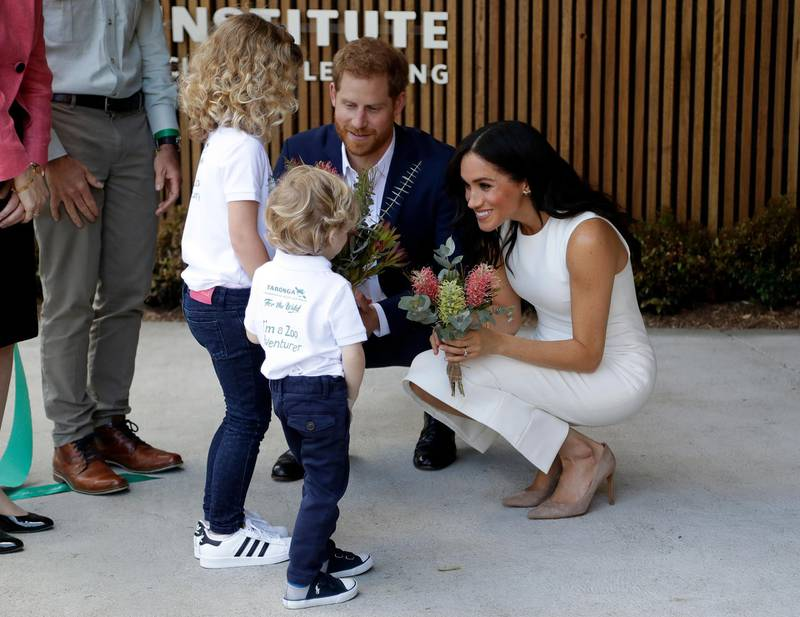 SYDNEY, AUSTRALIA - OCTOBER 16:  Prince Harry, Duke of Sussex and Meghan, Duchess of Sussex are presented with native flowers from children, Dasha Gallagher (L) and Finley Blue, during a ceremony at Taronga Zoo on October 16, 2018 in Sydney, Australia. The Duke and Duchess of Sussex are on their official 16-day Autumn tour visiting cities in Australia, Fiji, Tonga and New Zealand.  (Photo by Kristy Wigglesworth – Pool/Getty Images)