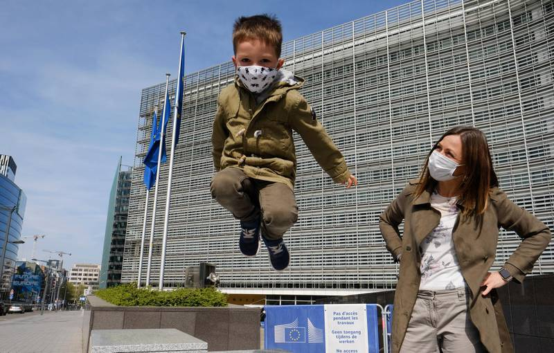 epa08363981 A mother and her son wearing face masks in front of European Commission headquarters during a press conference of European Council President Charles Michel and EU Commission President Ursula Von der Leyen on the Coronavirus pandemic in Brussels, Belgium, 15 April 2020.  EPA/OLIVIER HOSLET