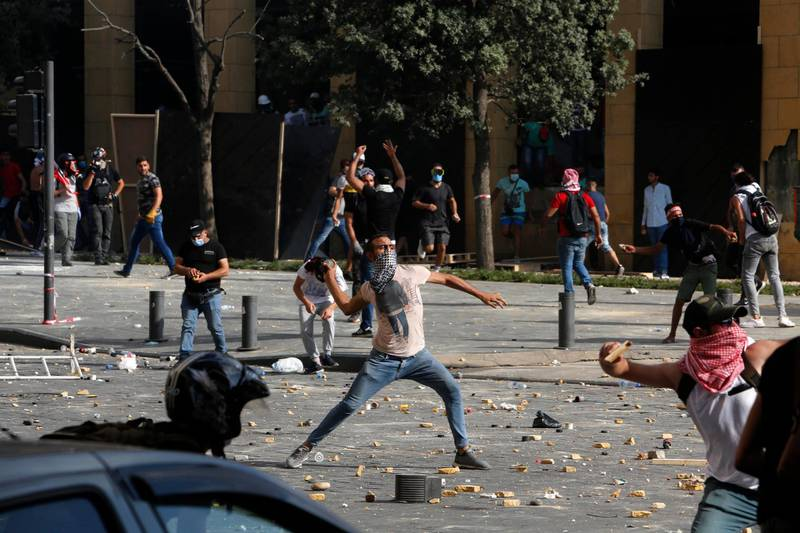 BEIRUT, LEBANON - AUGUST 08: Protesters throw stones during an anti-government demonstrations on August 8, 2020 in Beirut, Lebanon. The Lebanese capital is reeling from this week's massive explosion that killed at least 150 people, wounded thousands, and destroyed wide swaths of the city. Residents are demanding accountability for the blast, whose suspected cause was 2,700 tons of ammonium nitrate stored for years at the city's port. (Photo by Marwan Tahtah/Getty Images)