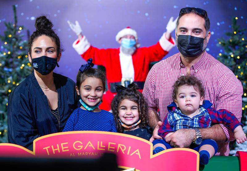 Abu Dhabi, United Arab Emirates, December 9, 2020.  The Nachar family pose with socially distanced Santa at the Winter Village, The Galleria Al Maryah Island.Victor Besa/The NationalSection:  NAFor:  Stock/Standalone