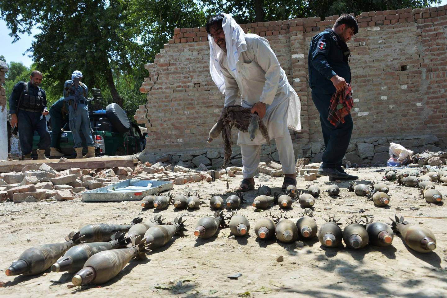 Afghan security officials inspect seized weapons near a damaged residential house from where a group of Islamic State (IS) gunmen were firing mortar shells while another group was raiding a prison, in Jalalabad on August 4, 2020. - At least 29 people were killed when gunmen attacked a jail in the eastern city of Jalalabad on August 3, shattering the relative calm of the final day of a three-day ceasefire between the Taliban and Afghan forces. (Photo by NOORULLAH SHIRZADA / AFP)