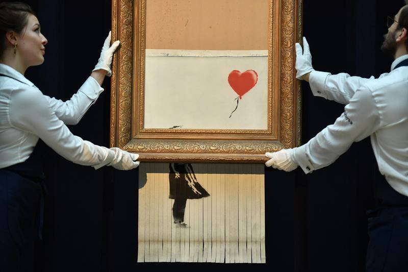 """Sotheby's employees pose with the newly completed work by artist Banksy entitled """"Love is in the Bin"""", a work that was created when the painting """"Girl with Balloon"""" was passed through a shredder in a surprise intervention by the artist, at Sotheby's auction house in London on October 12, 2018, following the work's sale. - The buyer of a work by street artist Banksy that was partially destroyed moments after it sold has gone through with the purchase, Sotheby's auction house said on October 11, 2018. The painting """"Girl with Balloon"""" was passed through a shredder hidden in the frame just after it went under the hammer last week for £1,042,000 ($1.4 million, 1.2 million euros). The modified version has now been certified by Banksy's authentication body Pest Control as a new piece of work in its own right, entitled """"Love is in the Bin"""". (Photo by Ben STANSALL / AFP) / RESTRICTED TO EDITORIAL USE - MANDATORY MENTION OF THE ARTIST UPON PUBLICATION - TO ILLUSTRATE THE EVENT AS SPECIFIED IN THE CAPTION"""