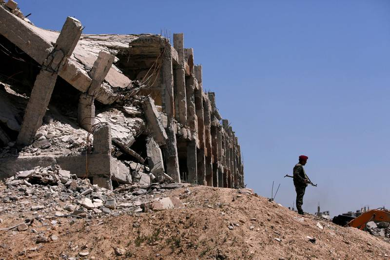 FILE PHOTO: A member of Syrian forces of President Bashar al Assad stands guard near destroyed buildings in Jobar, eastern Ghouta, in Damascus, Syria April 2, 2018. REUTERS/Omar Sanadiki/File Photo