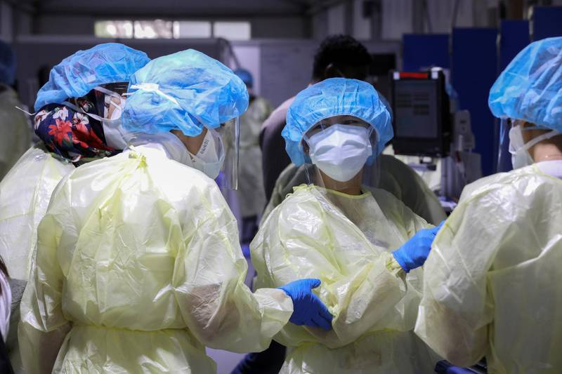 Nurses wearing protective equipment speak while testing patients, amid the coronavirus disease (COVID-19) outbreak, at the Cleveland Clinic hospital in Abu Dhabi, United Arab Emirates, April 20, 2020. REUTERS/Christopher Pike