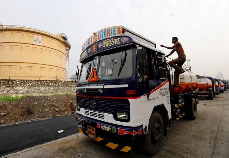 A man climbs an an oil tanker parked outside a fuel depot in Mumbai, India, October 6, 2017. REUTERS/ Danish Siddiqui