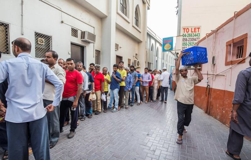 DUBAI,  UNITED ARAB EMIRATES, 20 May 2018 - People queueing to get  take away porridge for the iftar at Lootah Masjid Mosque, Deira, Dubai. Leslie Pableo for The National  for Ramola Talwar story