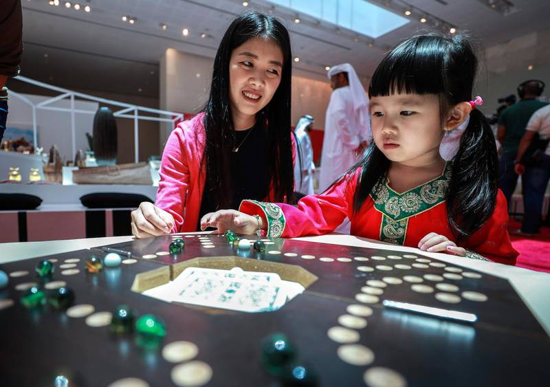 Abu Dhabi, U.A.E., July 17, 2018.   The Launch of China Week at Manarat Al Saadiyat with guests of honor, Noura Al Kaabi, Minister of Culture and Knowledge Development and Ni Jian, Ambassador of China.  --  A little girl plays with the Chinese Checkers game at the exhibition. Victor Besa / The NationalSection:  NAReporter:  John Dennehy