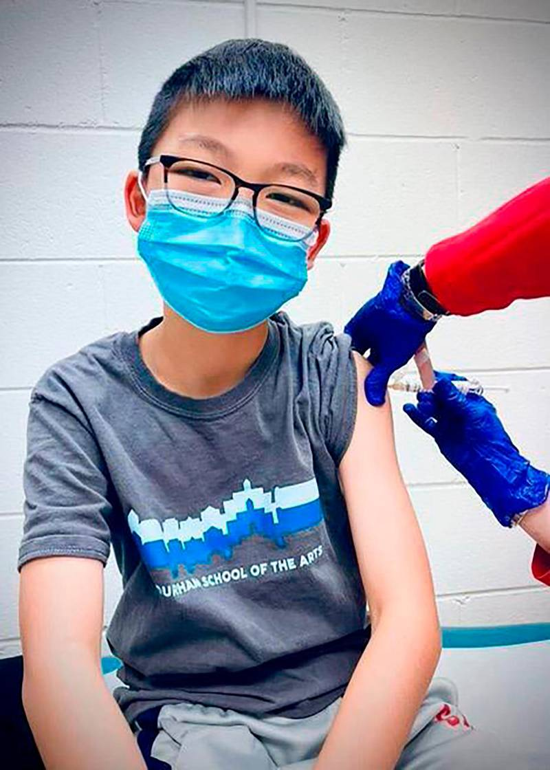 In this Dec. 22, 2020, photo, provided by Richard Chung, his son Caleb Chung receives the first dose of Pfizer coronavirus vaccine or placebo as a trial participant for kids ages 12-15, at Duke University Health System in Durham, N.C.  Pfizer says its COVID-19 vaccine is safe and strongly protective in kids as young as 12. The announcement Wednesday, March 31, 2021 marks a step toward possibly beginning shots in this age group before the next school year. (Richard Chung via AP)