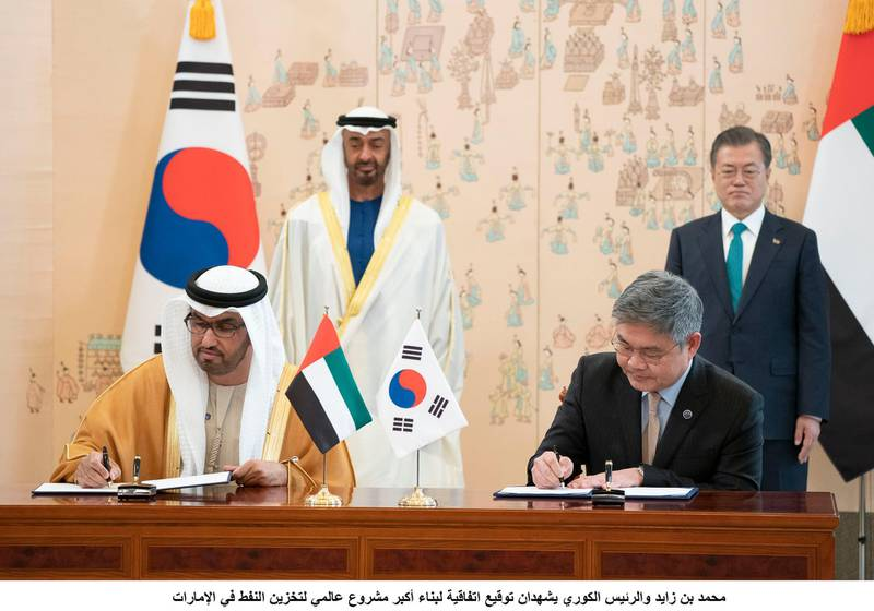 SEOUL, REPUBLIC OF KOREA (SOUTH KOREA)  - February 27, 2019: HH Sheikh Mohamed bin Zayed Al Nahyan, Crown Prince of Abu Dhabi and Deputy Supreme Commander of the UAE Armed Forces (back L) and Moon Jae-in, President of the Republic of Korea (South Korea) (back R), witness an MOU signing ceremony between ADNOC and SKEC to build the world's largest crude oil storage facility in Fujairah, at the Blue House. Seen signing on behalf of the UAE is HE Dr Sultan Ahmed Al Jaber, UAE Minister of State, Chairman of Masdar and CEO of ADNOC Group (L) and a Korean representative of SKEC (R). ( Rashed Al Mansoori / Ministry of Presidential Affairs )---