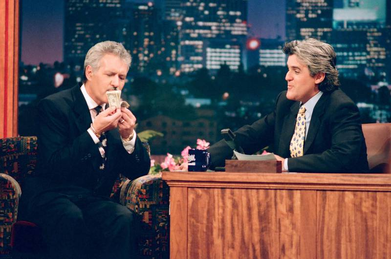 """THE TONIGHT SHOW WITH JAY LENO -- Episode 571 -- Pictured: (l-r) """"Jeopardy"""" host Alex Trebek with host Jay Leno during an interviewon November 14, 1994 -- (Photo by: Margaret Norton/NBCU Photo Bank/NBCUniversal via Getty Images via Getty Images)"""