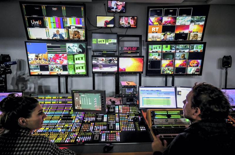 A picture taken on June 8, 2018 shows an unidentified directors of the Russia Today (RT) TV company at in their apparatus room in Moscow. (Photo by Yuri KADOBNOV / AFP)
