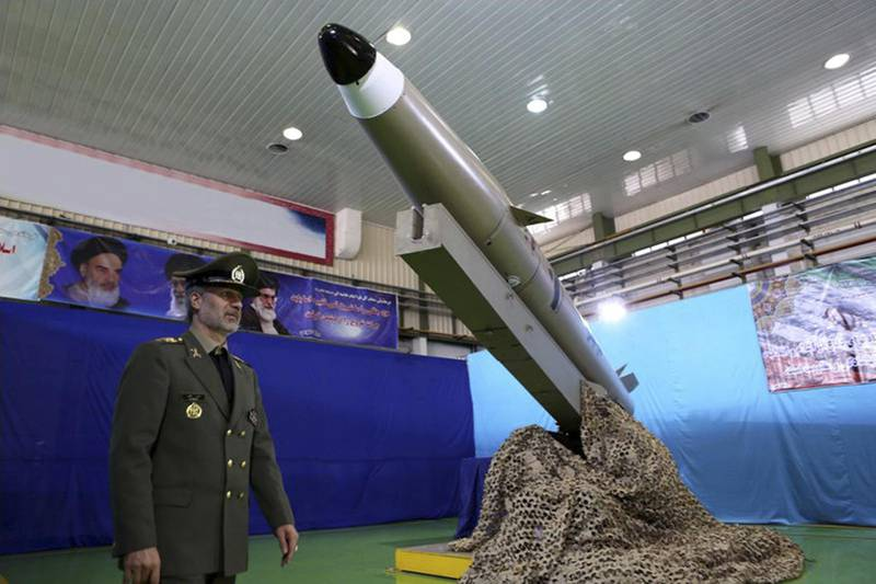 In this picture released by the official website of the Iranian Defense Ministry on Monday, Aug. 13, 2018, Defense Minister Gen. Amir Hatami walks past the missile Fateh-e Mobin, or Bright Conqueror, during inauguration of its production line at an undisclosed location, Iran. Iran on Monday said it launched a production line for a radar-evading, short range surface-to-surface missile capable of hitting targets in any weather condition. (Iranian Defense Ministry via AP)