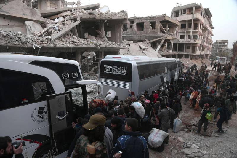 Syrians gather to board busses as they prepare to evacuate one of the few remaining rebel-held pockets in Arbin, in Eastern Ghouta, on the outskirts of the Syrian capital Damascus, on March 24, 2018. Syrian rebels and civilians prepared to evacuate the penultimate opposition-held pocket of Eastern Ghouta, as the government moved ever closer to securing the outskirts of the capital. / AFP PHOTO / ABDULMONAM EASSA