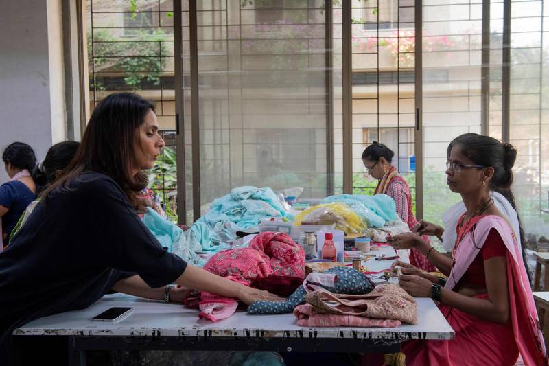 In this photo taken on February 14, 2020, fashion designer Anita Dongre (L) interacts with a worker at her factory on the outskirts of Mumbai. With stores in India and New York, multiple clothing brands and a global celebrity following, fashion designer Anita Dongre is a feminist powerhouse in a male-dominated industry. But her true ambition is to create an environmentally sustainable company, she says. - TO GO WITH Women-activism-India-fashion-economy-environment,INTERVIEW by Ammu Kannampilly  / AFP / Laurène Becquart / TO GO WITH Women-activism-India-fashion-economy-environment,INTERVIEW by Ammu Kannampilly