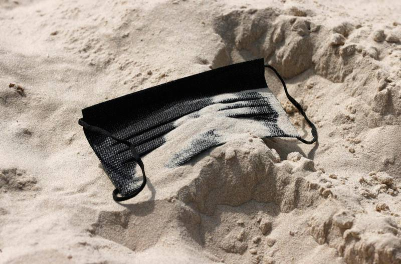Sand covers a discarded protective face mask at the beach in the Israeli coastal city of Tel Aviv on April 18, 2021, after authorities announced that face masks for COVID-19 prevention were no longer needed outside. With more than half of the population fully vaccinated in one of the world's fastest COVID-19 inoculation campaigns, the number of coronavirus cases in Israel fell from some 10,000 new infections per day in mid-January to about 200 cases per day, which triggered an announcement from the Health Department on April 15 that face masks are no longer mandatory outdoors. / AFP / JACK GUEZ
