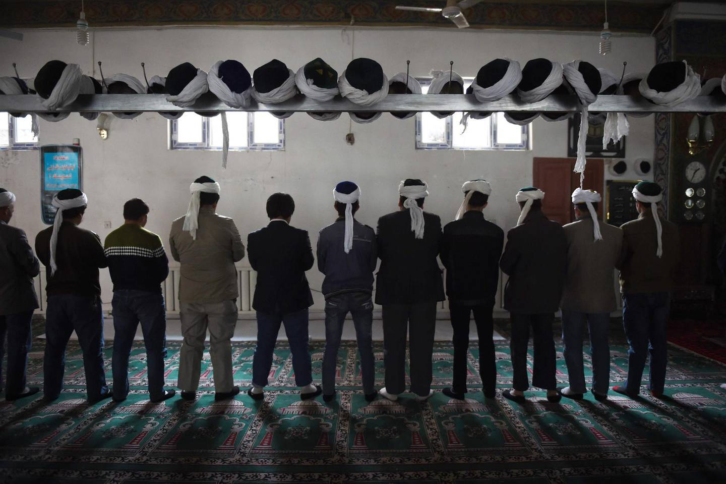 """TOPSHOT - This photo taken on April 16, 2015 shows Uighur men praying in a mosque in Hotan, in China's western Xinjiang region.  The prefecture in the region's south has seen an explosion in the construction of """"vocational training"""" centres for the region's Muslim minorities. But the centres have come under international scrutiny, with rights activists describing them as political re-education camps holding as many as one million ethnic Uighurs and other Muslim minorities. - TO GO WITH China-politics-rights-Xinjiang, FOCUS by Ben Dooley  / AFP / Greg Baker / TO GO WITH China-politics-rights-Xinjiang, FOCUS by Ben Dooley"""