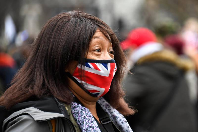 A woman wears a Union flag themed face mask as an anti-lockdown demonstration takes place in Parliament Square, in London, Monday, Dec. 14, 2020. Britain launched its vaccination program this month after becoming the first country to give emergency approval to the Pfizer-BioNtech vaccine, and authorities plan to dispense 800,000 doses in the first phase. (AP Photo/Alberto Pezzali)