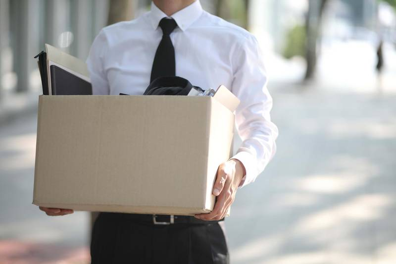 Close-up Of Unemployed Businessperson Carrying Cardboard Box. Getty Images