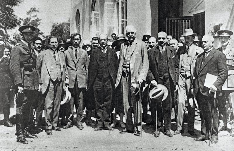 """(FILES) This handout file photo taken in 1925 and obtained from the Israeli Government Press Office (GPO) on October 24, 2017, shows Arthur Balfour (C), former British prime minister, and Chaim Weizmann (3rd-R), the then future first President of Israel, visiting Tel Aviv. Britain's Balfour Declaration turns 100 this week, hailed by Israel for helping lead to its founding, but viewed by Palestinians as contributing to a catastrophe that stole their land. The November 2, 1917 declaration by then British foreign minister Arthur Balfour said his government viewed """"with favour the establishment in Palestine of a national home for the Jewish people"""".  / AFP PHOTO / GPO / Handout"""