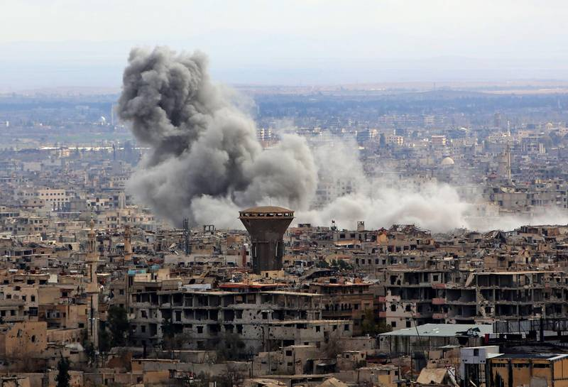 """A general view taken from Damascus shows smoke rising from the rebel-held enclave of Eastern Ghouta following fresh air strikes and rocket fire on February 27, 2018.  A fledgling """"humanitarian pause"""" announced by Russia in Syria's rebel-held enclave of Eastern Ghouta was rattled by fresh air strikes and rocket fire, several sources said. / AFP PHOTO / STRINGER"""