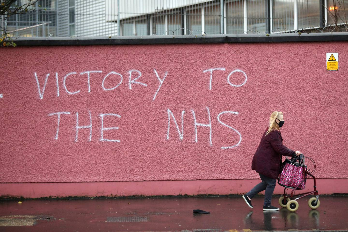 A woman walks past graffiti with the words Victory to the NHS (National Health Service) on a wall at the Royal Victoria Hospital, one of several hospitals around Britain that are handling the initial phase of a COVID-19 immunization program, in West Belfast, Northern Ireland, Tuesday, Dec. 8, 2020. British health authorities rolled out the first doses of a widely tested and independently reviewed COVID-19 vaccine Tuesday, starting a global immunization program that is expected to gain momentum as more serums win approval. (AP Photo/Peter Morrison)